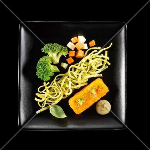 Vegetarian dish of noddles with pesto,pureed carrots and crisp vegetables on a black background