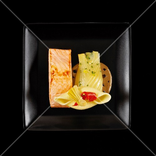 Piece of salmon with stewed fennel and creamy mushroom sauce on a black background