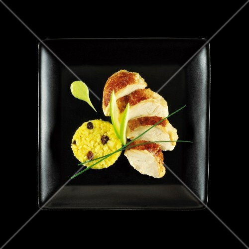 Sliced chicken breast,green apple and saffron rice on a black background