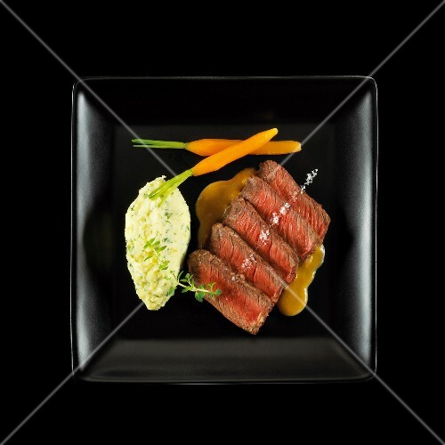 Fillet of beef with carrot gravy and homemade herb mashed potato quenelle on a black background