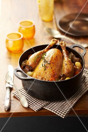 Roasted capon with mushrooms,carrots,onions and potatoes in a casserole dish
