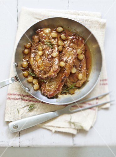 Caramelized rib roasts with small onions and rosemary