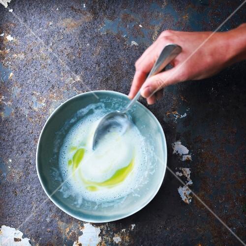 Person preparing a foamy buttermilk sauce