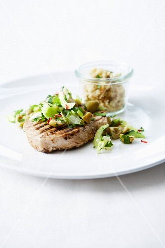 Grilled tuna steak with celey stalks, herbs and green olives, semolina