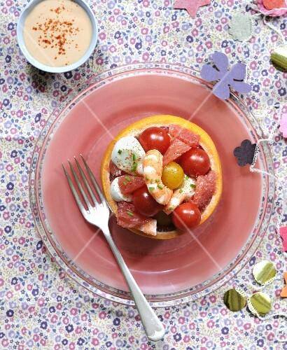 Tomato,shrimp,mozzarella ball and grapefruit salad in a grpefruit skin