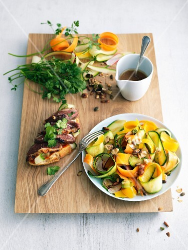 Thin strips of zucchinis and carrots with dried fruit and seeds, duck magret on toast