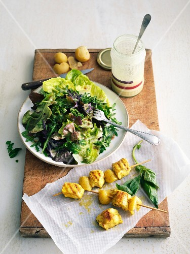 Mixed lettuce and fresh herb salad with white dressing, curried chicken-confit citrus skewers