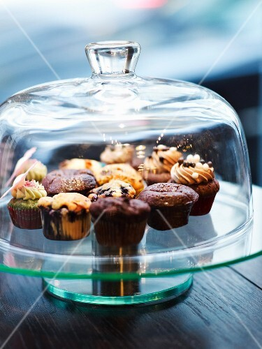 Assortment of muffins under a glass dome