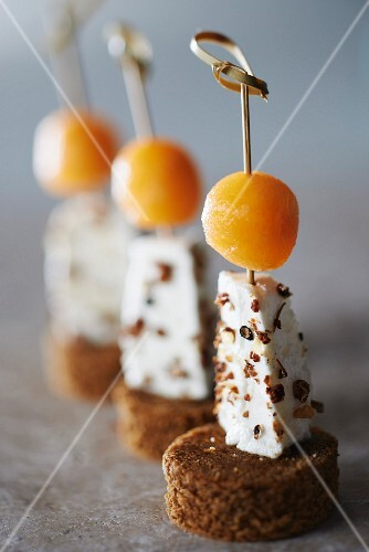 Gingerbread, blackcurrant peppery Petit Billy and melon ball appetizers on sticks