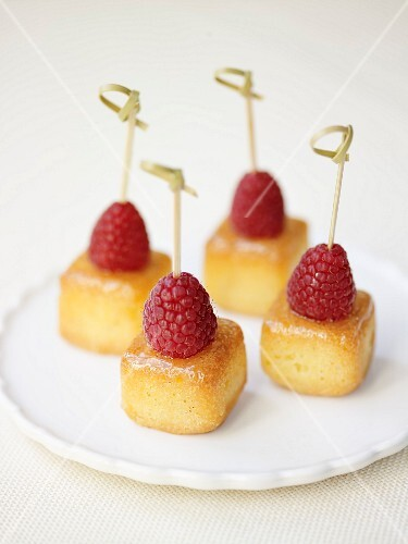 Mini baba cubes topped with raspberries on sticks