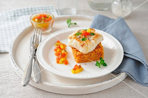Piece of cod on a square timbale of saffron rice and virgin sauce