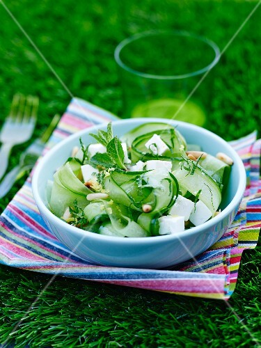 A salad with cucumber strips, diced feta, mint and pine nuts
