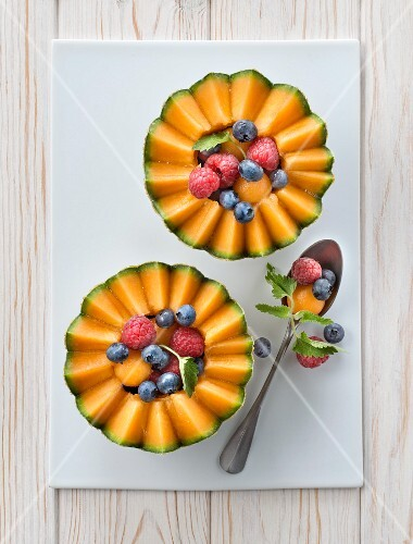 Melon garnished with raspberries and blackcurrants