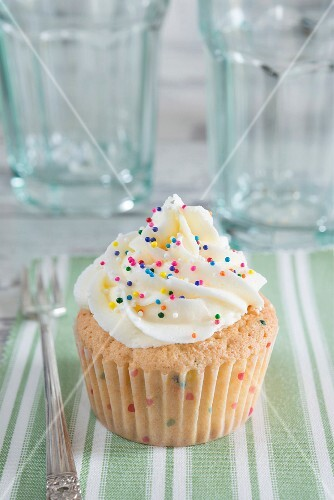 Cupcake sprinkled with multicolored sugar droplets