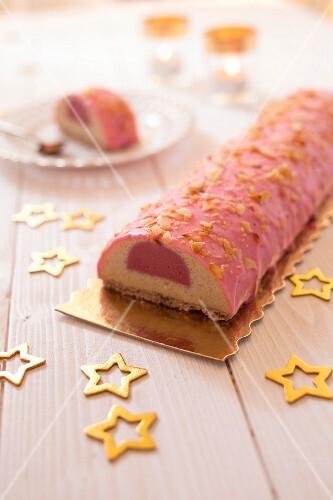 Vanilla-raspberry Chritmas log cake coated with pink icing