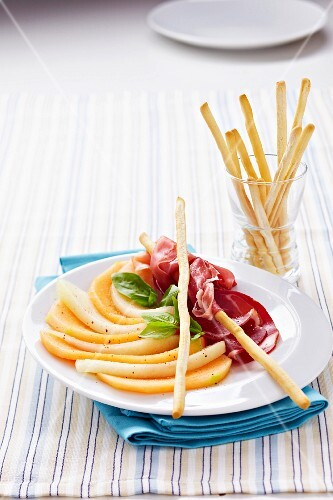 Thinly sliced honeydew melon,raw ham and breadsticks