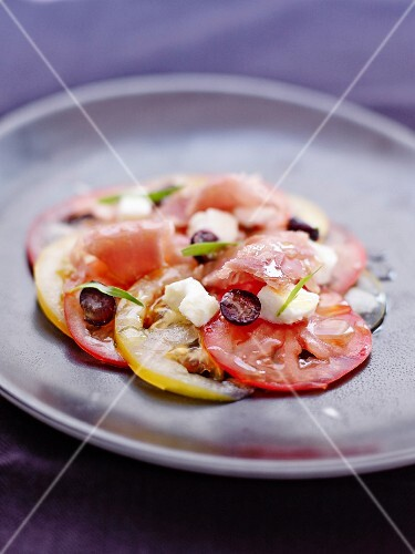 Red and yellow tomato carpaccio with raw tuna,cranberries and feta