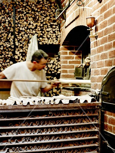 Baker placing bread in a wood oven