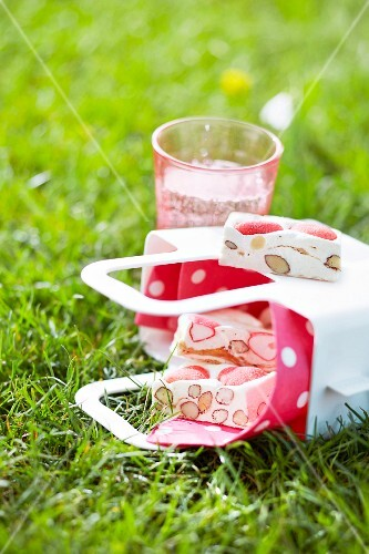 Paper cones of nougat in the grass outdoors