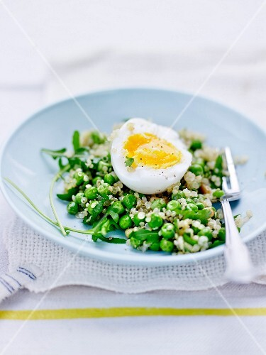 Pea,quinoa and pine nut salad topped with a soft-boiled egg