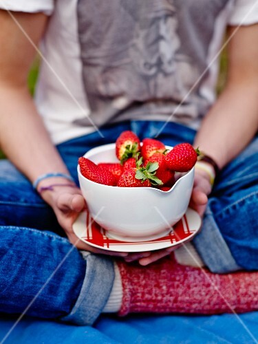 Person holding a bowl of strawberries