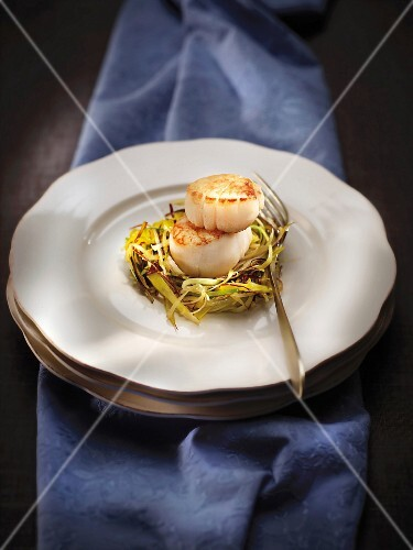 Grilled scallops on a bed of thinly sliced leeks