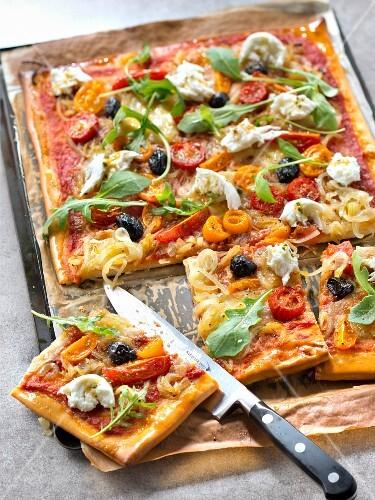 Pizza with onion confit, marinated tomatoes, arugula and mozzarella