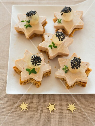 Gingerbread and foie gras stars topped with white grapes and black sesame seeds