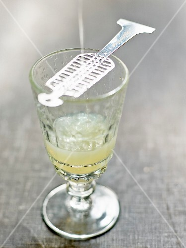 Diluting a sugarlump on a spoon in th glass of Absinthe