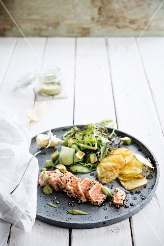 Salmon tataki with a sesame seed crust and wasabi cream, chips and a cucumber and avocado salad