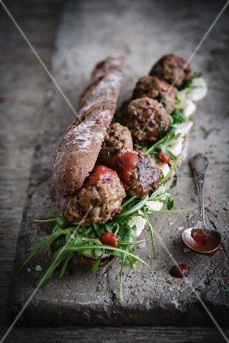 Wholemeal baguette with meatballs, ketchup, rocket and cheese