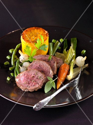 Saddle of lamb with thyme,carrot flan and sauteed vegetables