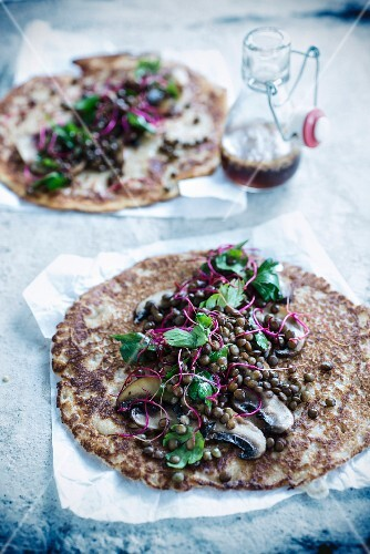 Cheese pancake garnished with lentils and mushrooms