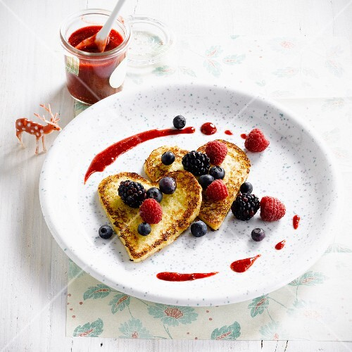 Heart-shaped pancakes with summer berries and coulis
