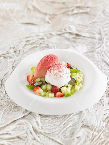 A salad with cucumber, black grapes and fruits of the forest with yoghurt mousse
