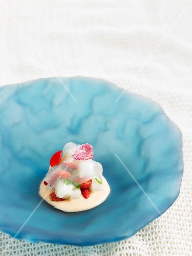 Transparent wild strawberry jelly with fresh coconut and melon cream with edible geraniums