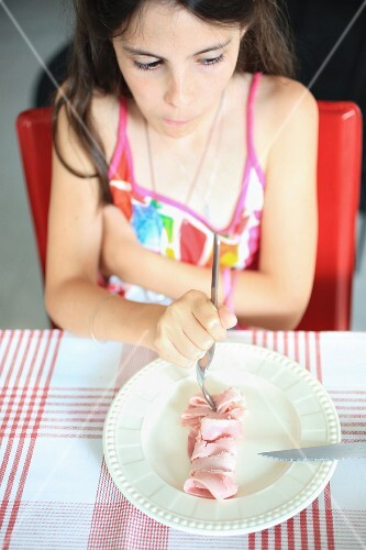 A young girl eating ham with a fork