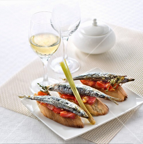 Bruschetta with fried sardines, tomatoes and lemongrass and a glass of fruity white wine