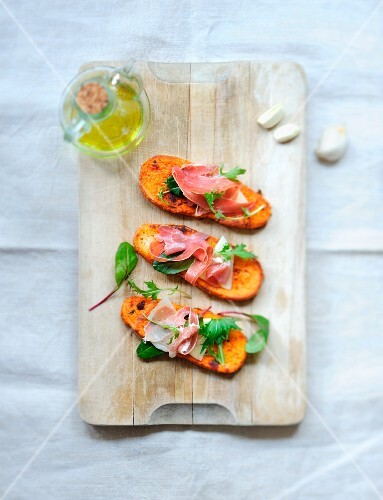 Tomato and garlic french toast with raw ham and lettuce