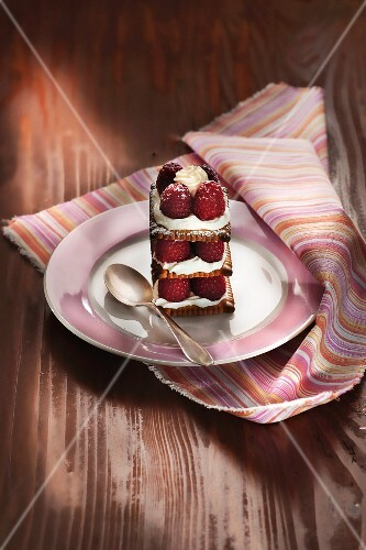 A mille feuille made from butter biscuits with raspberries and cream