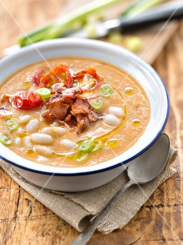 Thick white haricot bean and tomato soup with smoked bacon