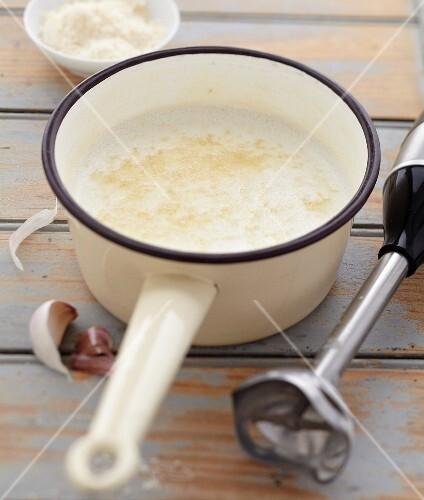 Preparing parmesan cream with garlic