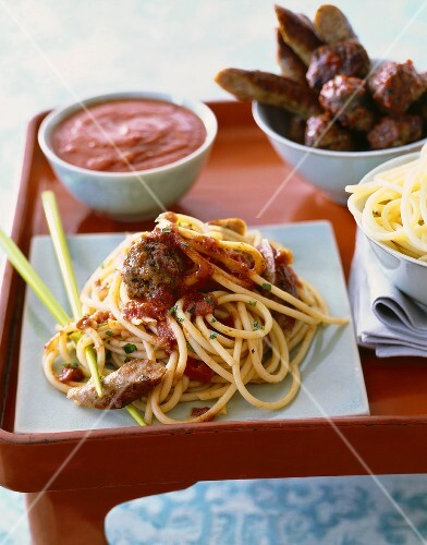 Serving of Spaghetti with Sausage, Meatballs and Marinara Sauce; Bowl of Pasta and Bowls of Toppings