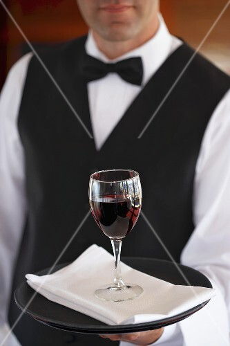 Waiter serving a glass of red wine