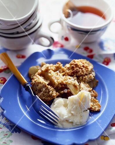 Serving of Apple Crisp with Vanilla Ice Cream; Cup of Tea
