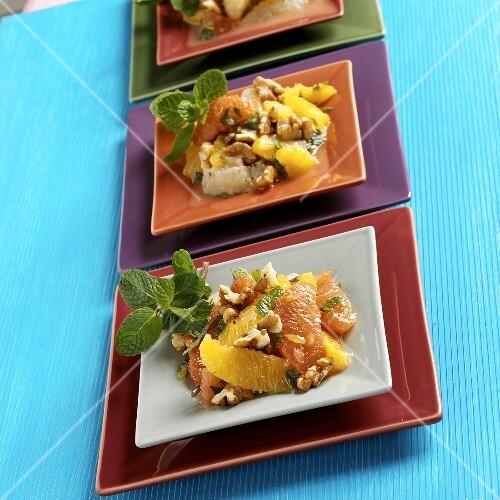 Citrus Walnut Salad Served on Three Colorful Square Plates, Mint Garnish