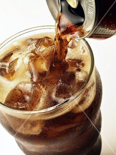 Pouring Cola into a Glass with Ice Cubes from a Can