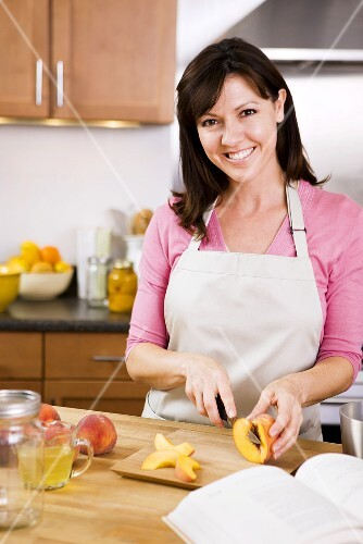 Woman Preparing Peaches for Homemade Canned Peaches; In Kitchen