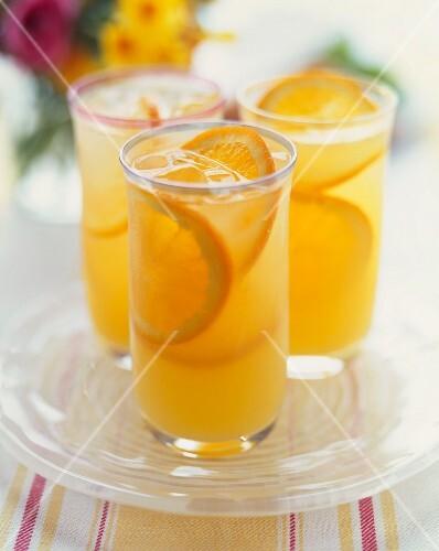 Three Glasses of Sparkling Orangeade with Orange Slice Garnishes