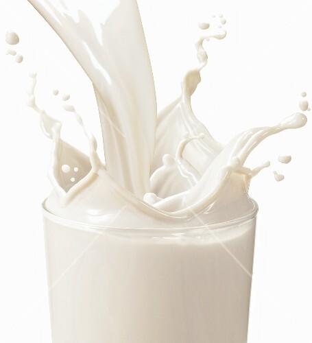 Vanilla Milk Pouring into a Glass; Splashing